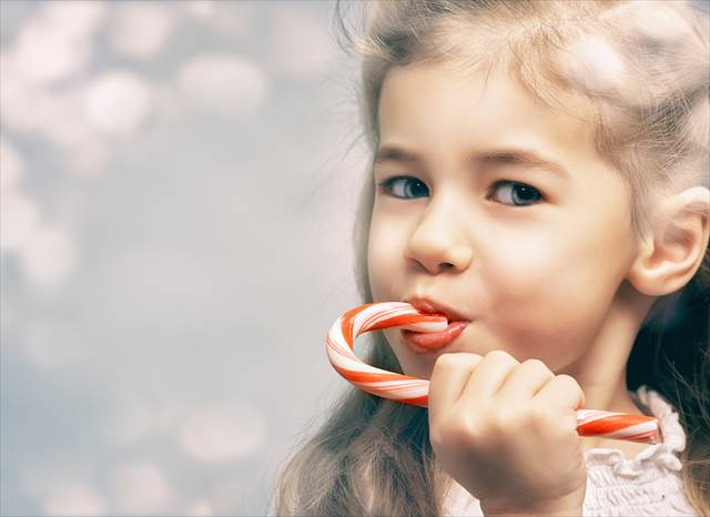 little girl eats a candy bar