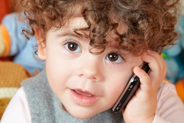 Two year old girl with curly hair talking on phone.