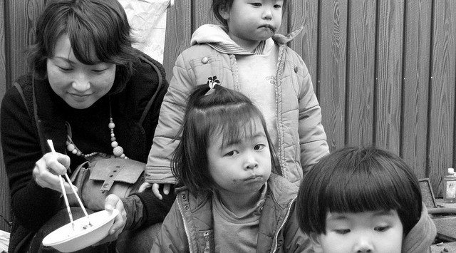 Mother and her children enjoying mochi (traditional New Year's food), outdoor mochi-making party, Aogaki, Japan.