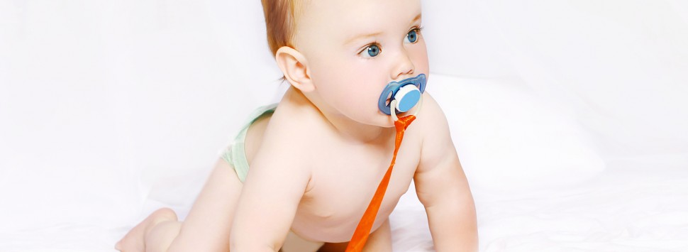 Cute baby with pacifier on the bed at home